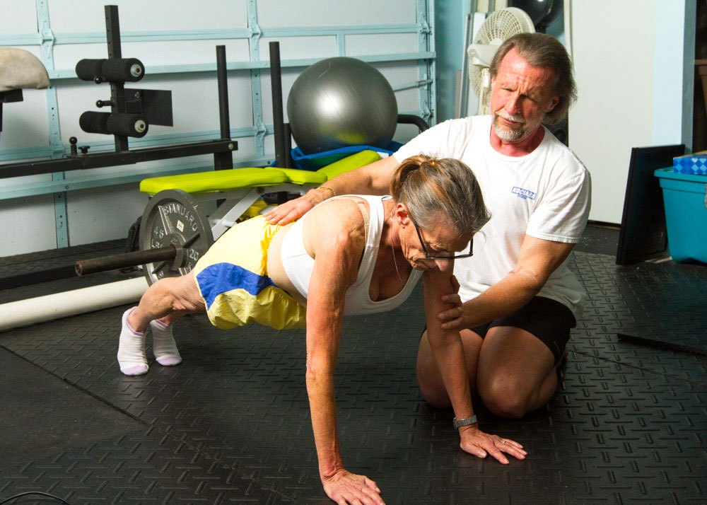 Bill Kociaba, HKC Instructor, trains a client who is performing a plank