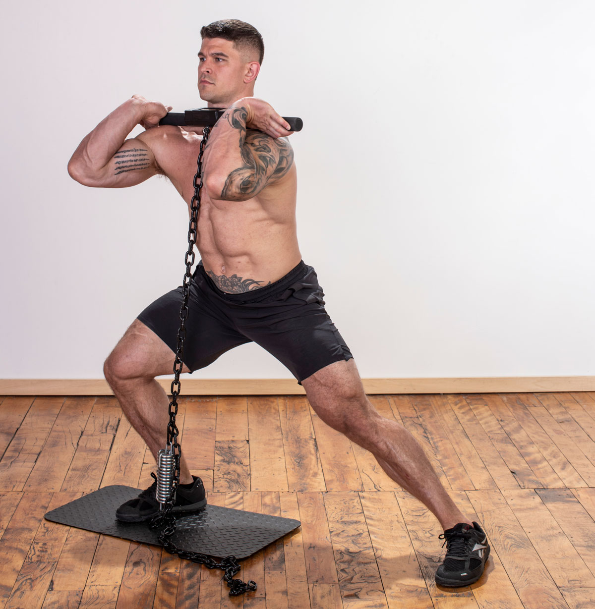 muscular male athlete performing an Isochain Side Lunge