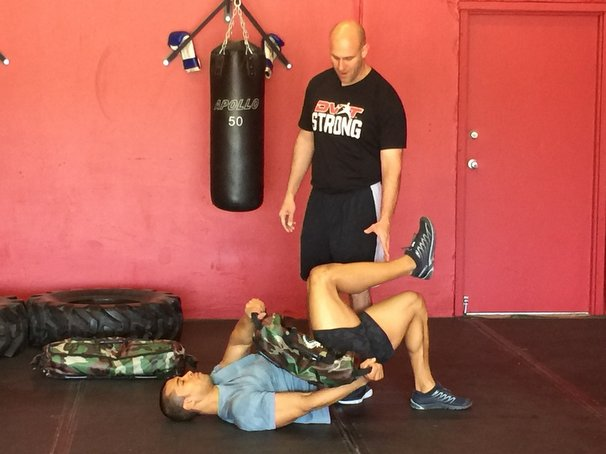 Josh Henkin Coaching the Ultimate Sandbag Glute Bridge