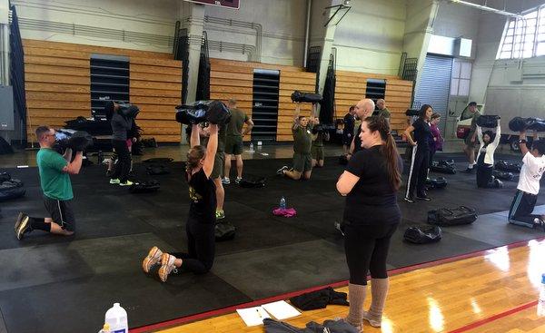 Faith Martin leading a class in Ultimate Sandbag kneeling overhead press